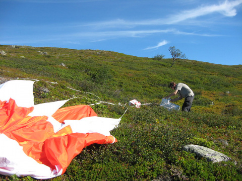 Researcher untangles a orange and white scientific balloon in a field from 2017